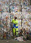 Man shoveling in front of a wall of recycling. Stock Photo - Premium Royalty-Free, Artist: Arcaid, Code: 649-01608514