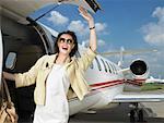 Happy female exiting corporate Jet.