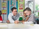 Male teacher sitting at work table with girl and boy Stock Photo - Premium Royalty-Freenull, Code: 649-01610327
