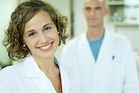 Female doctor smiling, male colleague in background, portrait Stock Photo - Premium Royalty-Freenull, Code: 632-01612763