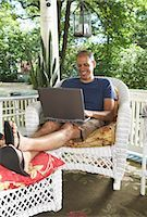Man Sitting on Porch using Laptop Computer    Stock Photo - Premium Royalty-Freenull, Code: 600-01614300