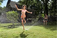 Family playing in backyard with sprinkler    Stock Photo - Premium Royalty-Freenull, Code: 600-01614310