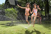 Family playing in backyard with sprinkler    Stock Photo - Premium Royalty-Freenull, Code: 600-01614312
