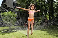 Family playing in backyard with sprinkler Stock Photo - Premium Royalty-Freenull, Code: 600-01614315