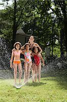 Portrait of Mother with Children Playing in Backyard with Sprinkler    Stock Photo - Premium Royalty-Freenull, Code: 600-01614318