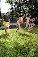 Family Playing in Backyard with Sprinkler    Stock Photo - Premium Royalty-Freenull, Code: 600-01614321