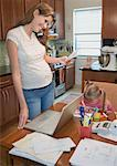 Woman Paying Bills and Girl Colouring in Kitchen    Stock Photo - Premium Rights-Managed, Artist: Raoul Minsart, Code: 700-01630386