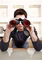 Man with binoculars in eyeglass store Stock Photo - Premium Royalty-Freenull, Code: 644-01631061