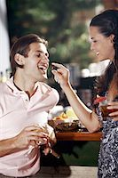 Woman feeding man in a bar Stock Photo - Premium Royalty-Freenull, Code: 644-01631535