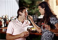 Woman feeding man in a bar Stock Photo - Premium Royalty-Freenull, Code: 644-01631536