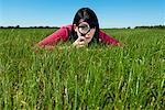 Woman Examining Grass With Magnifying Glass