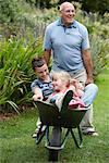 Grandfather Pushing Grandchildren in Wheelbarrow    Stock Photo - Premium Royalty-Free, Artist: Masterfile, Code: 600-01645159