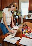 Mother in Kitchen, Talking on Telephone and Using Laptop Computer