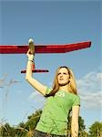 Teenage girl (16-17) standing in field,holding model glider,low angle Stock Photo - Premium Royalty-Free, Artist: Cusp and Flirt, Code: 613-01649379