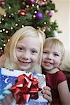 Two young girls holding present near Christmas tree Stock Photo - Premium Royalty-Free, Artist: Marie Blum, Code: 653-01656570