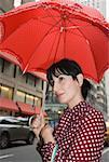 Young woman wearing a polka dot dress and holding a red umbrella in city street, New York City Stock Photo - Premium Royalty-Free, Artist: Blue Images Online, Code: 653-01657881