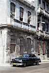 Vintage car parked in front of run-down building, Havana, Cuba
