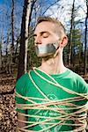 Man standing in the woods bound in rope and with adhesive tape covering his mouth Stock Photo - Premium Royalty-Free, Artist: Westend61, Code: 653-01662796