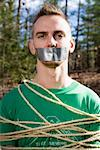 Man standing in the woods bound in rope and with adhesive tape covering his mouth Stock Photo - Premium Royalty-Free, Artist: Westend61, Code: 653-01662801