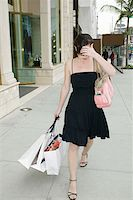 A woman walking down the street with shopping bags and covering her face, Rodeo Drive, Los Angeles, California, USA Stock Photo - Premium Royalty-Freenull, Code: 653-01664709