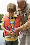 Man Helping Boy with Lifejacket