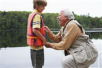 Man Helping Boy with Lifejacket    Stock Photo - Premium Royalty-Freenull, Code: 600-01694161