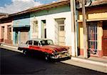An old fashioned car parked on a street in Cuba
