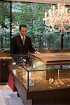 A businessman looking in a display cabinet in a jewelers Stock Photo - Premium Royalty-Free, Artist: Blend Images, Code: 653-01698708