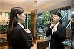 A woman adjusting her blouse in the mirror Stock Photo - Premium Royalty-Free, Artist: Blend Images, Code: 653-01698712