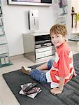 Boy in living room next to remotes and DVDs Stock Photo - Premium Royalty-Free, Artist: Masterfile, Code: 635-01706267
