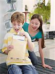 Young boy opening package while girl watches Stock Photo - Premium Royalty-Free, Artist: J. A. Kraulis, Code: 635-01706270