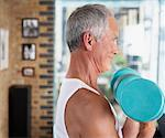 Man lifting dumbbells in living room Stock Photo - Premium Royalty-Free, Artist: Darryl Leniuk, Code: 635-01706868