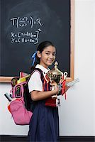 Girl with trophy by blackboard in classroom Stock Photo - Premium Royalty-Freenull, Code: 635-01707663