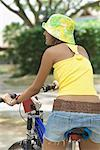 Rear view of a young woman riding a bicycle Stock Photo - Premium Royalty-Freenull, Code: 630-01708053