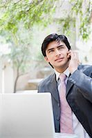 Businessman standing in front of a laptop and talking on a mobile phone Stock Photo - Premium Royalty-Freenull, Code: 630-01708498
