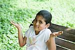 Portrait of a girl shrugging and sitting on a branch Stock Photo - Premium Royalty-Free, Artist: Cultura RM               , Code: 630-01709087