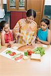 Mid adult woman making sandwich with her daughters
