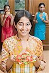 Close-up of a mid adult woman holding a sandwich with her daughters in the background