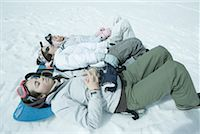 Three sisters lying on snow with heads resting on snowboard Stock Photo - Premium Royalty-Freenull, Code: 633-01713724