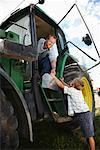 Boy Giving Lunchbox to Father in Tractor    Stock Photo - Premium Royalty-Free, Artist: Masterfile, Code: 600-01716028