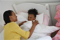 Mother Tucking Daughter into Bed    Stock Photo - Premium Royalty-Freenull, Code: 600-01717970
