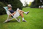 Man Sitting in Lawn Chair, Reading Book