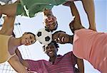 Adults huddled with soccer ball Stock Photo - Premium Royalty-Free, Artist: Masterfile, Code: 621-01727917