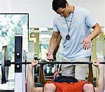 Two men in gym, one assisting other during weightlifting Stock Photo - Premium Royalty-Free, Artist: Paul Eekhoff, Code: 613-01731201