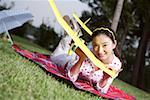 Portrait of young woman lying on front and holding glider Stock Photo - Premium Royalty-Free, Artist: Cusp and Flirt, Code: 642-01733464