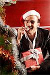Young man holding gift, sitting near Christmas Stock Photo - Premium Royalty-Free, Artist: Marie Blum, Code: 642-01733489