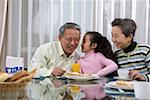 Senior couple sharing food with granddaughter Stock Photo - Premium Royalty-Free, Artist: foodanddrinkphotos, Code: 642-01735001