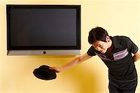 plasma - Fashionable young man bowing in front of TV Stock Photo - Premium Royalty-Freenull, Code: 642-01736857