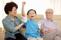 Senior couple with grandson sitting in sofa Stock Photo - Premium Royalty-Freenull, Code: 642-01736941