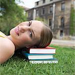 Student lying on pile of books on lawn, portrait, head and shoulders Stock Photo - Premium Royalty-Freenull, Code: 618-01738127